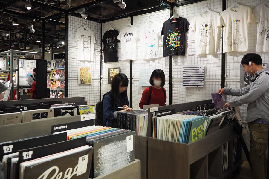 レコードショップのように陳列されたバンドTシャツ約1000点。壁にはSuchmosやMrs. GREEN APPLE、tricotなどのサイン入りTシャツの展示も