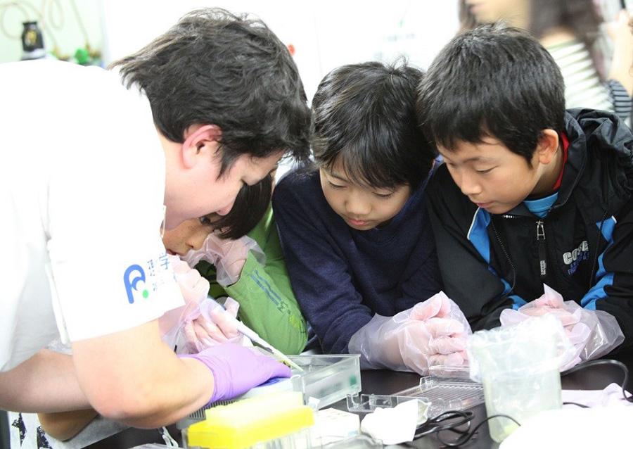 犯罪捜査や遺伝子診断の際に使われる「電気泳動」操作の一部を体験するDNA実験コーナー。子どもたちは夢中に 写真提供:神戸市