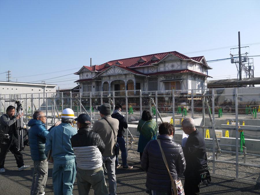 28日の最初の移動工事には地元の人も多く集まり、レールの上の旧駅舎を慎重に見学していた