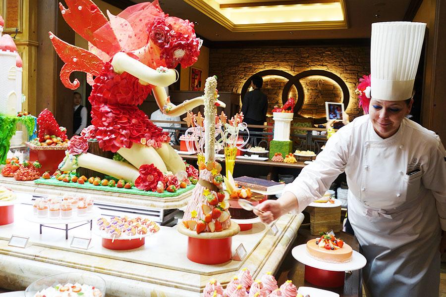 マジックをテーマとしたブッフェテーブル。シェフが「魔法のほうき」型のケーキをすくうデモンストレーションを披露