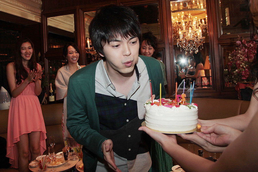 キャバクラ嬢役の女性たちによって運ばれた誕生日ケーキのろうそくを消す林遣都