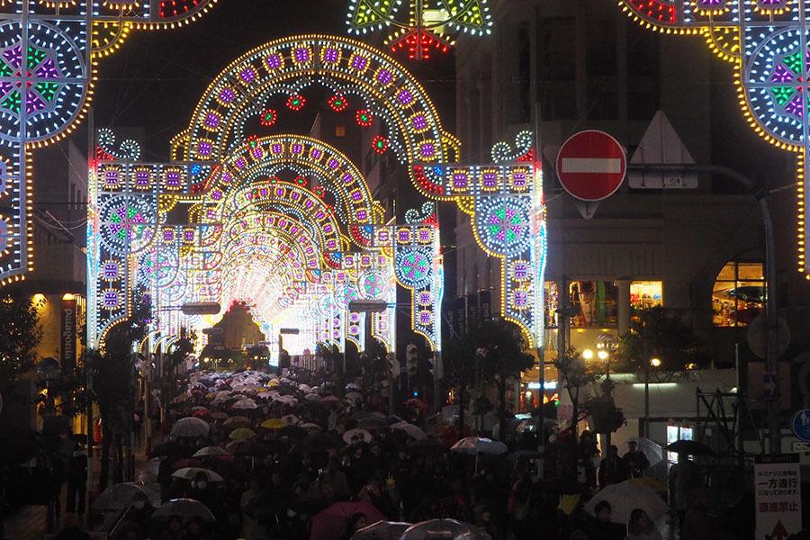 270メートル続く仲町通りの作品のなかを、雨のなか、傘をさして歩く人々(8日、神戸市)