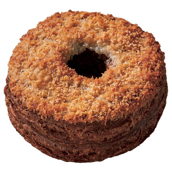 フライしたココア風味のクロワッサン生地にビターキャラメルクリームをサンドし、表面をグレーズでコーティング。ココナツをトッピングし、オーブンで焼き上げ、サクサクとした食感に仕上げた「クロワッサンドーナツショコラ トーステッドココナツ(194円)」