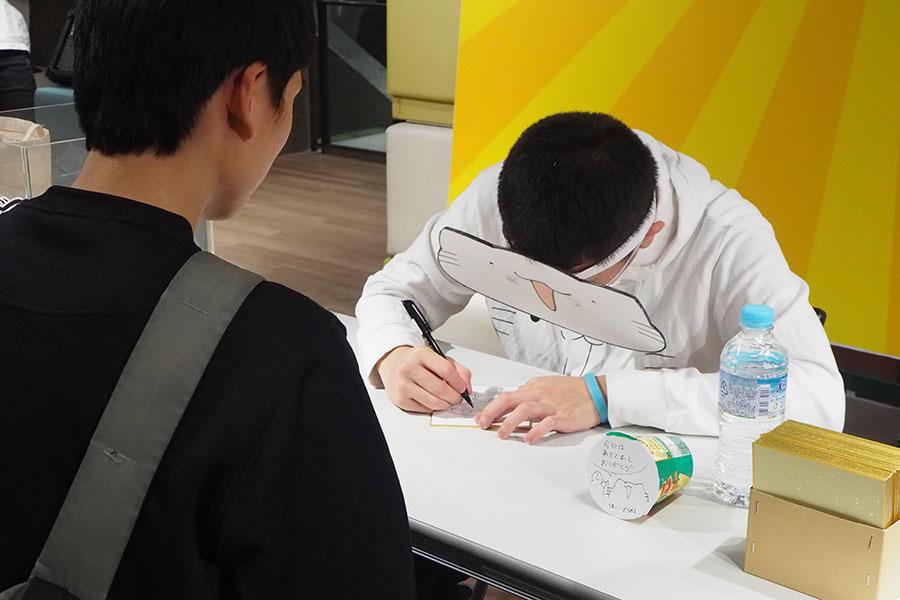 1人1人のリクエストに答えてサインとイラストを描くからめる(24日、大阪市内)
