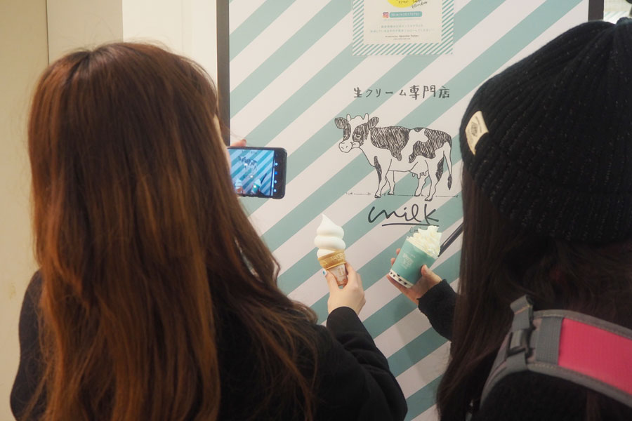 ミルキーパフェとソフトクリームを購入し、ロゴマークの前で写真を撮る女性たち