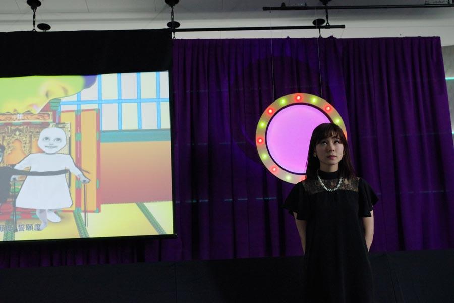 作品を説明する笹岡由梨子。「自分にとって死って大きなテーマ」と制作された作品は、自分の顔で作った表情を埋め込んで映像化した