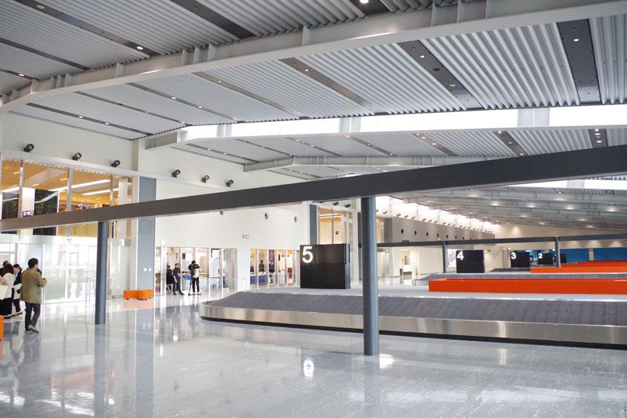 広大なスペースに荷物受け取り用のベルトコンベアが8つ並ぶ、到着口の出口付近