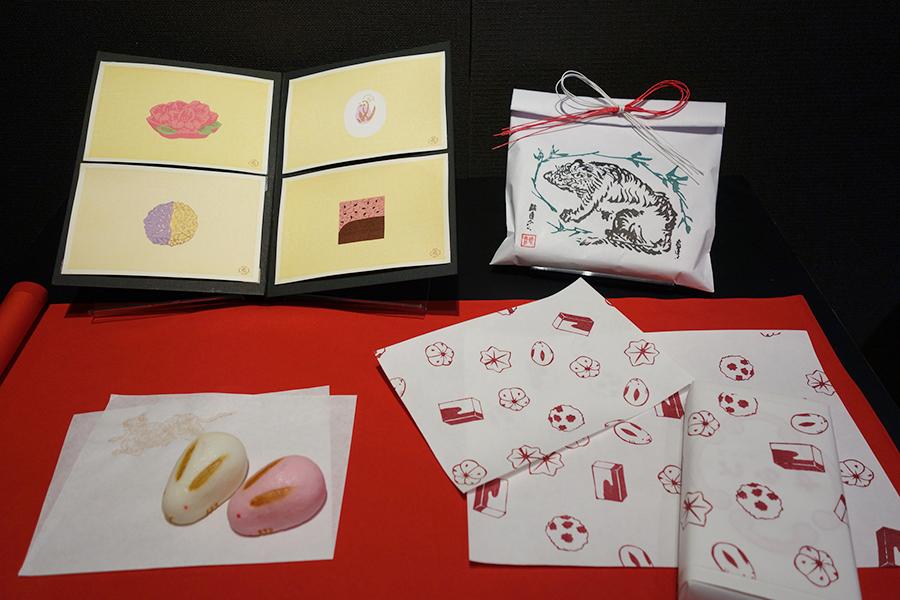 「虎屋」のさまざまなお菓子をモチーフに、「竹笹堂」がデザインした掛紙(右下)。期間中、虎屋一条店でのみ、申し出ればこちらをかけてもらえる