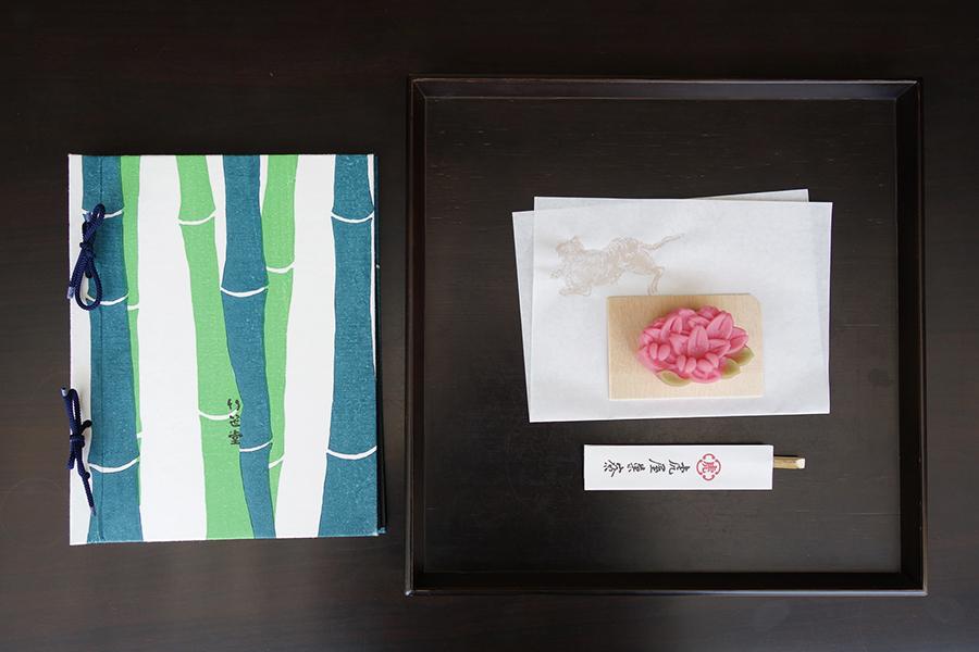お菓子のラインアップは、半月ごとに入れ替わる。つつじをかたどった白あん入りの羊羹製、「岩根の錦」。飲み物付きで1,242円〜。メニューも一つずつ異なるデザインを楽しめる