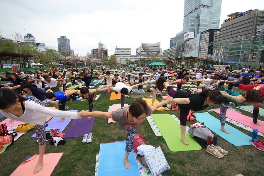 街なかにある広い公園で300人が一緒になってヨガを体験