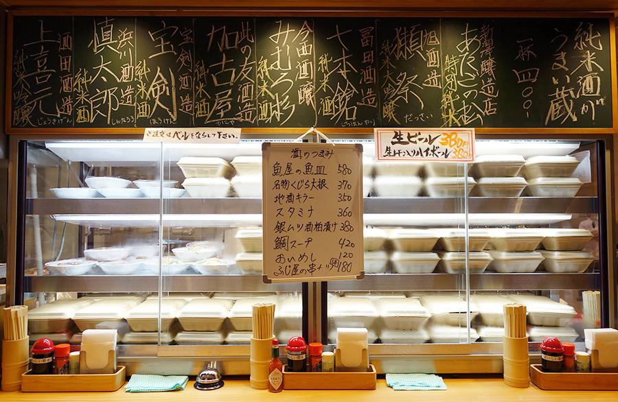 立ち喰い魚 ふじ屋では、その日おすすめのメニューが並ぶ。立ち食い用のカウンタースペースもあり、のれんで顔が隠れるのもポイント