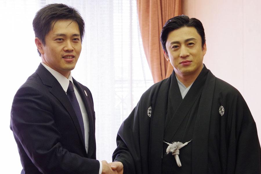 がっちりと握手を交わす吉村市長(左)と松本幸四郎
