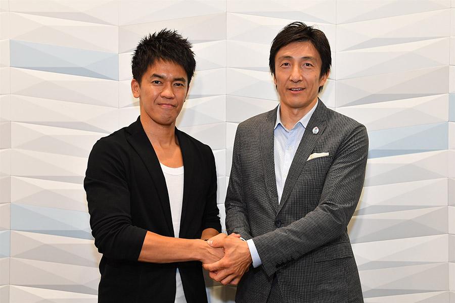 がっちりと握手を交わす武井壮(左)と朝原宣治氏