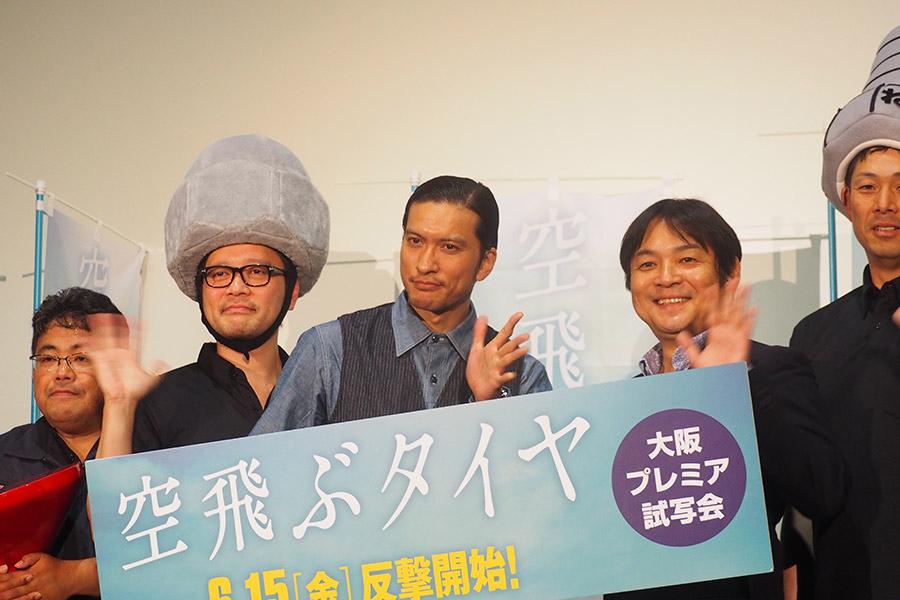ねじの被り物をした東大阪チームと写真撮影に挑んだ長瀬智也(中央)と本木克英監督(右から2番目)(1日・大阪市内)