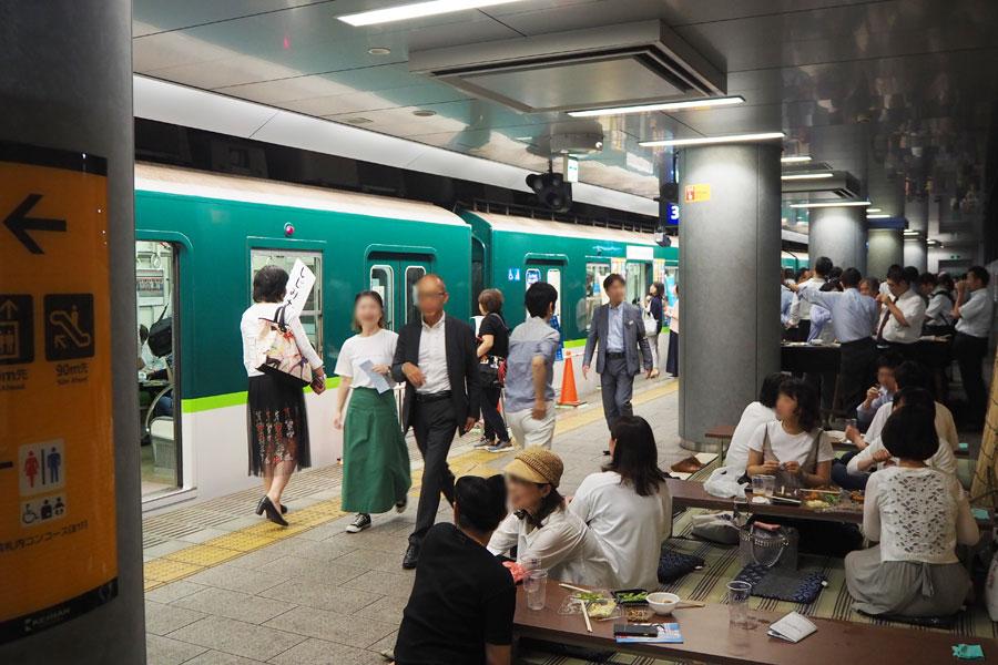 ホームの納涼床席で、靴を脱いでビールを楽しむ人々(21日、中之島駅構内)