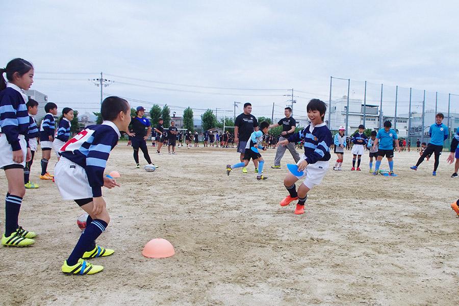 NTTドコモレッドハリケーンズの社会人選手たちによるラグビークリニックで一生懸命指導を受ける子どもたち(10日・大阪市内)