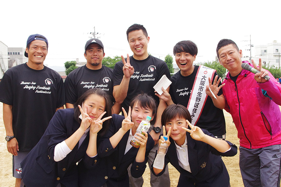 後方左から、NTTドコモレッドハリケーンズの才口悠太選手と吉田伸介選手、芸人・松永真也、生野区住みます芸人・田津原理音、芸人・ぼんちきよし。前列は、開会式の国歌斉唱を歌った東生野中学校校合唱部の女子学生たち(10日・大阪市内)