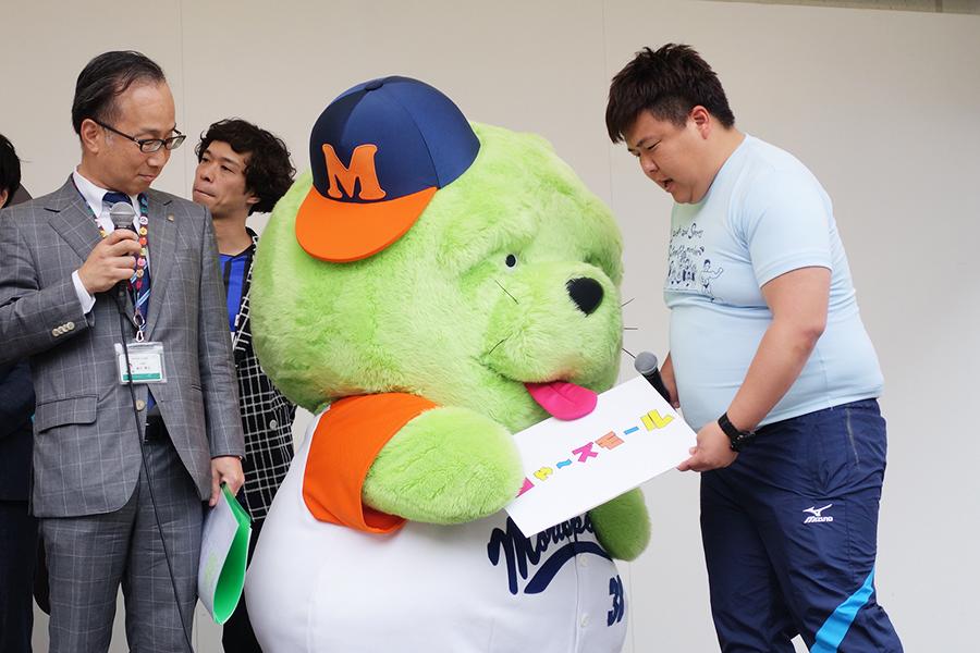 執行委員の滝川さん、モリスペクターに『チャーズモール』のボードを持たせようとするミサイルマン・西代