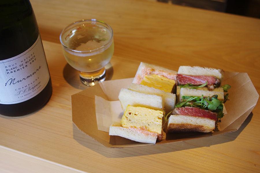 イベント『銅座モーニング』で提供された「鮨 三心」のイワシサンドと卵サンド(800円)、「hapo」のスパークリングリングワイン(700円)