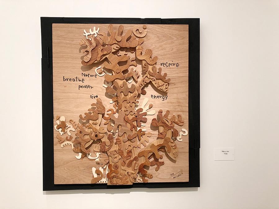 手の形にカットした木片で樹木のように描いた作品 REACH OUT Tree