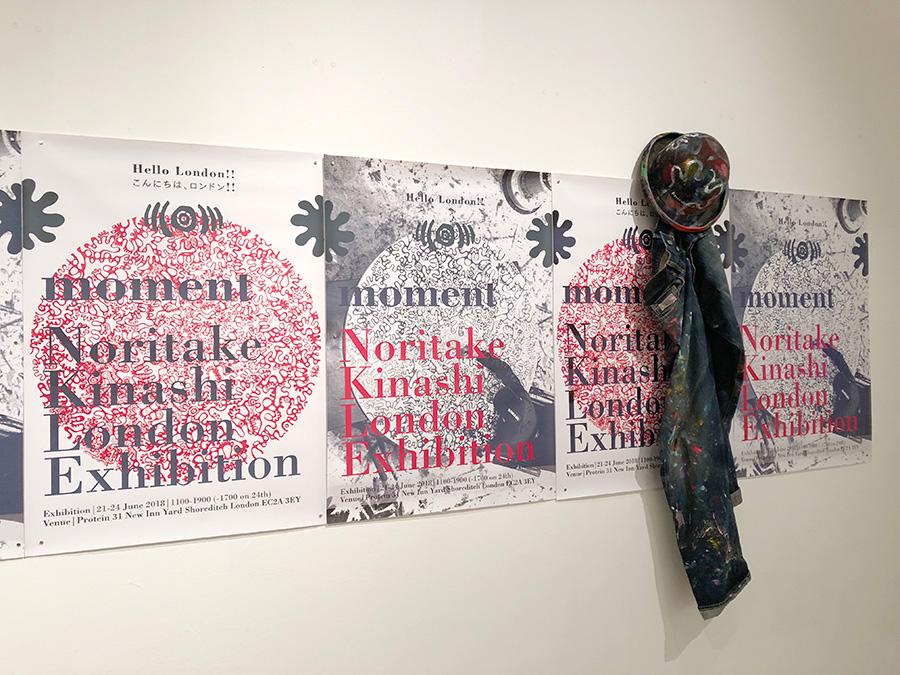 ロンドンで開催された個展のポスターと、絵を描くときに木梨さんが着用したジーンズとハット。冒頭に展示されている