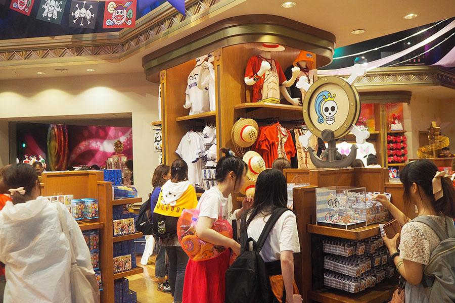 イニシャルモチーフのグッズが並ぶ売り場に集まる女性ファン(5日、ユニバーサル・スタジオ・ジャパン)