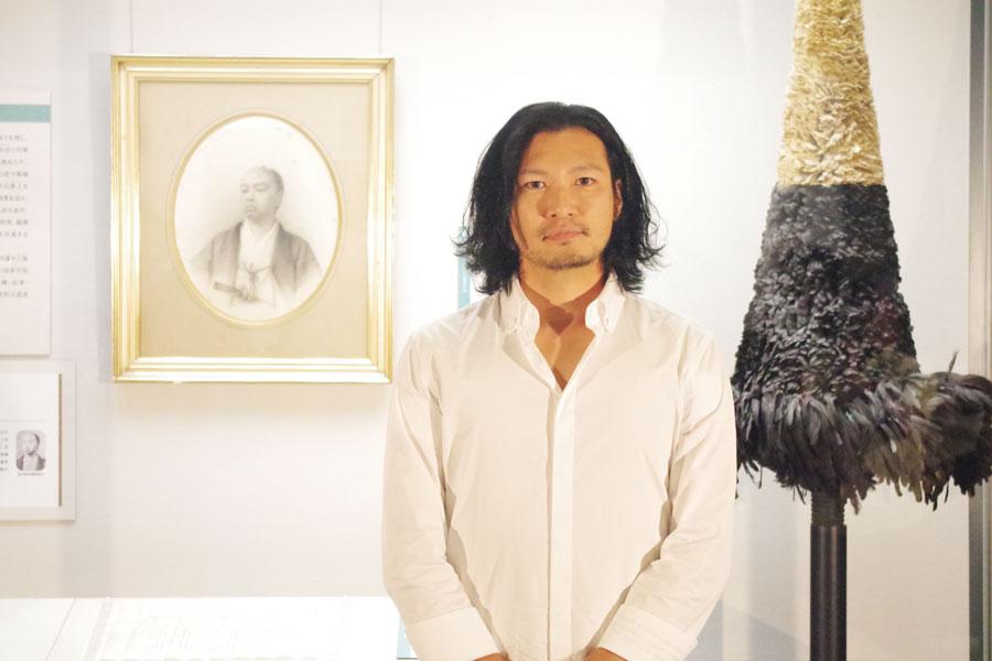 久光の肖像画をバックに会見を開いた青山