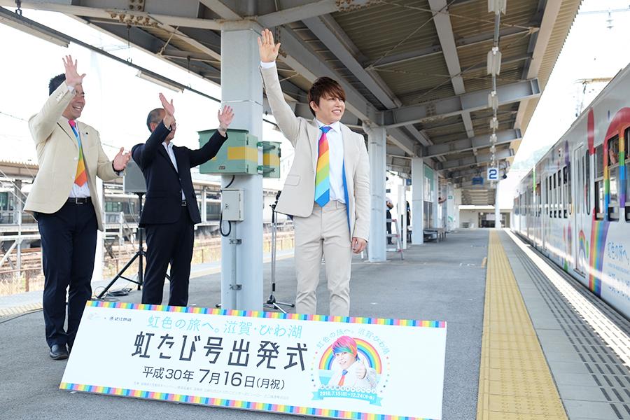 自身の顔でラッピングされた「虹たび号」に手を振る西川