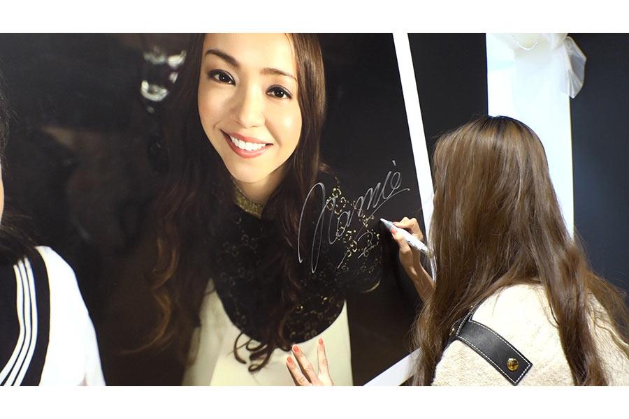 巨大パネルにサインする歌手・安室奈美恵