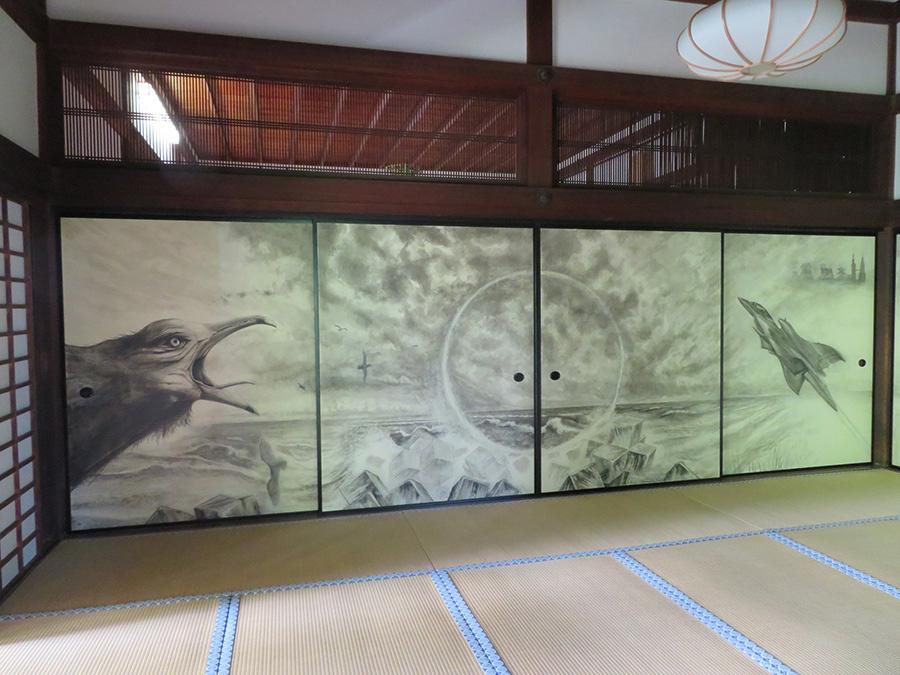山賀博之「かろうじて生きている」(部分) モチーフは日本海。ウミネコと戦闘機に挟まれた中央の円は、己の心を移す窓を意味する