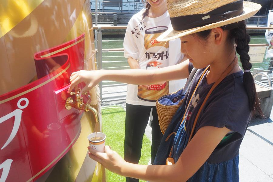 コップにカフェオーレを注ぐ埼玉から来たという女の子。カフェオーレはコップなみなみまで入れてOKとのこと