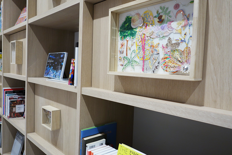 育児書のほか、写真集や美術書も並ぶライブラリーには清川あさみの作品も展示