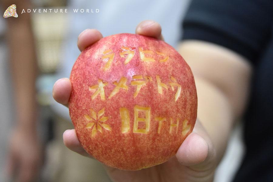 「ラウヒン オメデトウ 18TH」と刻まれた誕生日プレゼントのリンゴ