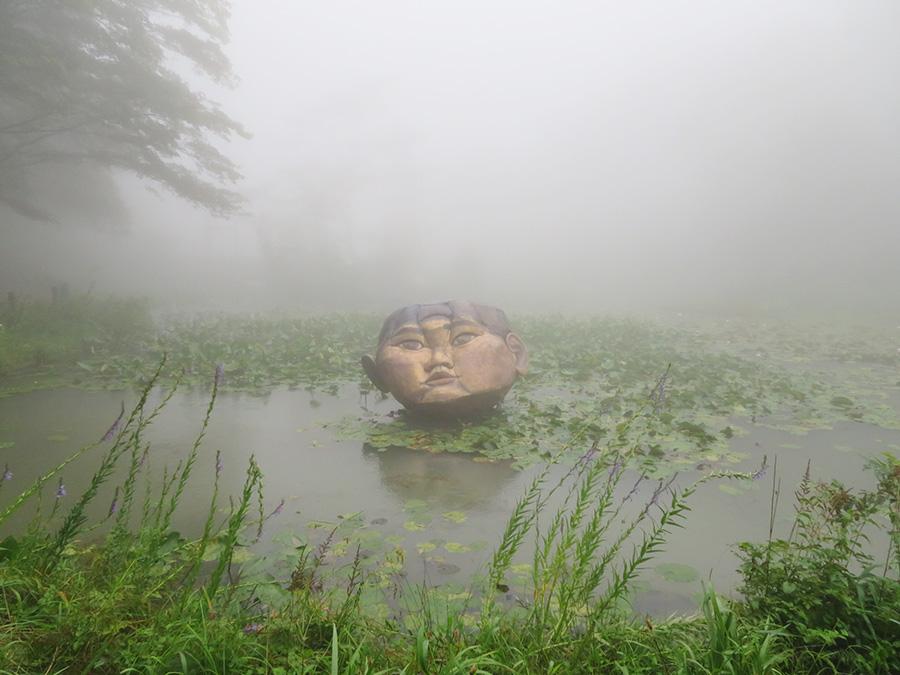 釜本幸治《浮標-淡い寄る辺》 会場:六甲高山植物園 森の中の池に突然現れる巨大な顔がインパクト大。実物はかなり大きい