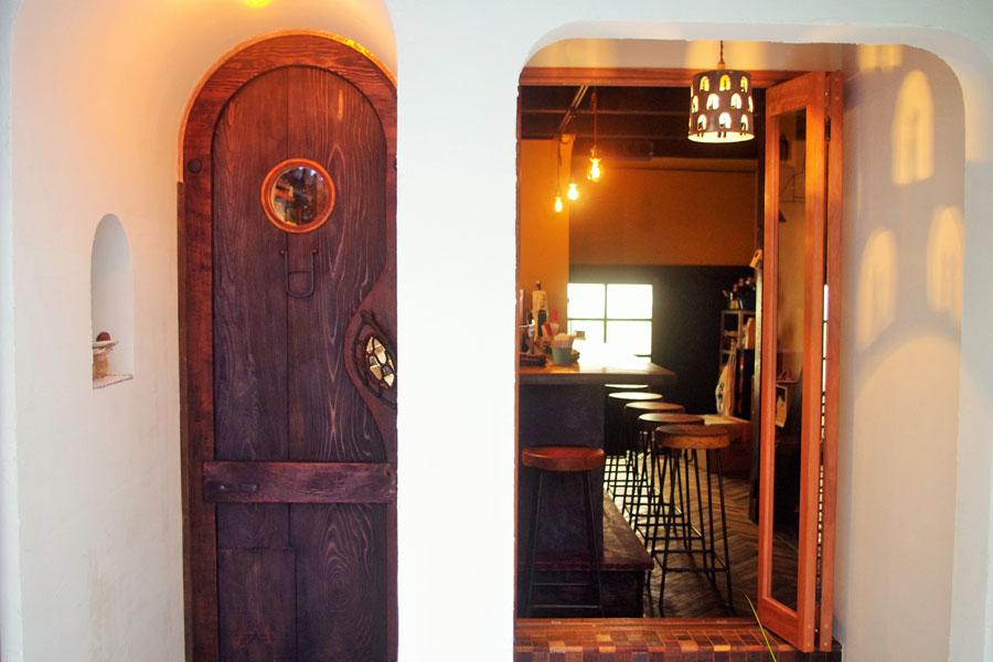古道具の金具や古材で作られた扉と手作りのランプ。白い壁にはランプの柄が浮かび上がる