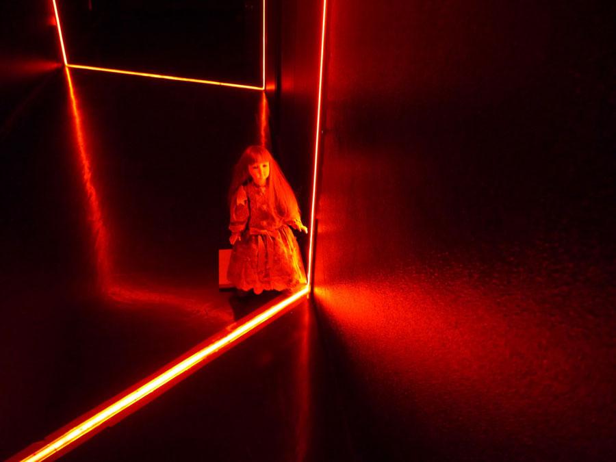 暗闇に赤いライトが灯るだけでホラー仕様に。そして、なにげにおかれた人形が恐怖心をあおる