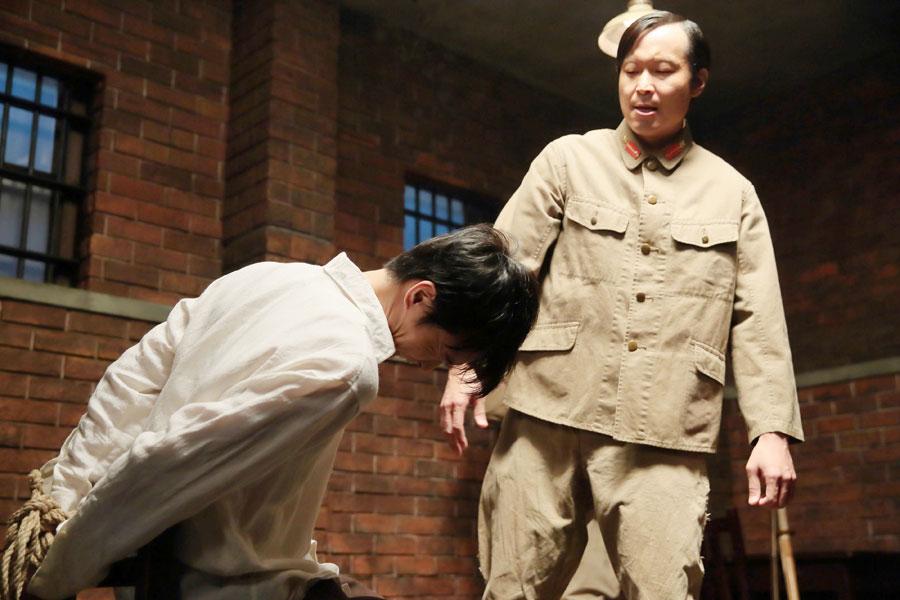 大阪憲兵分隊庁舎。無実の罪を着せられた萬平(左・長谷川博己)は、取調室で憲兵・村城啓治(平原テツ)から暴行を受ける