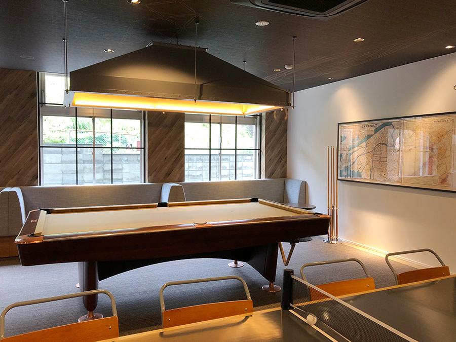 ビリヤードやテーブル兼卓球台が置かれたラウンジスペース