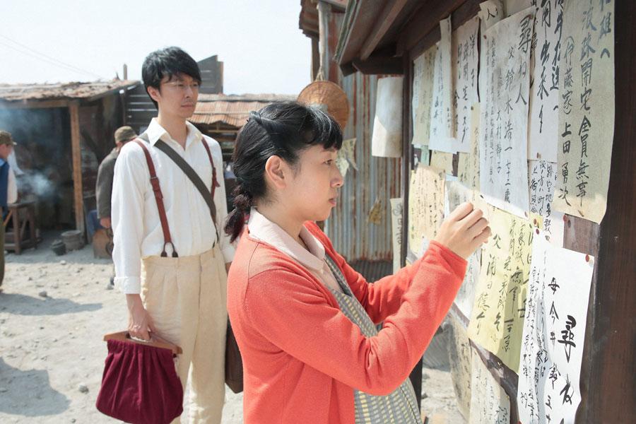 大阪市内の街角で、家出中の母・鈴(松坂慶子)の張り紙を貼る(安藤サクラ)と萬平(長谷川博己)