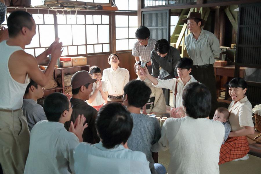 泉大津の自宅・倉庫にて、家族や従業員らに、ついに完成したダネイホンを高々と掲げる萬平(中央・長谷川博己)