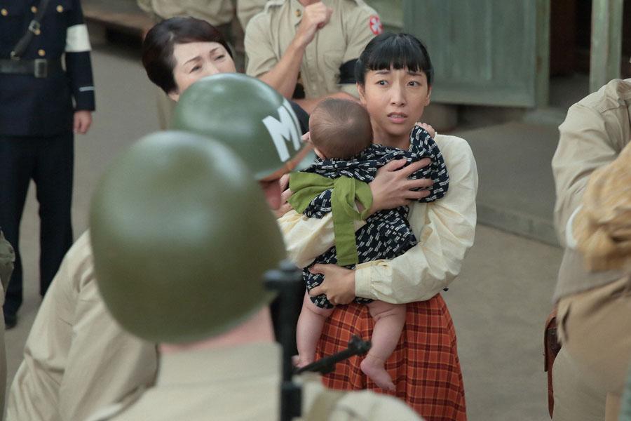 進駐軍から「全員逮捕だ」と告げられ、萬平らが連行されるも、福子(中央・安藤サクラ)は幼子を抱えながらオロオロするばかり