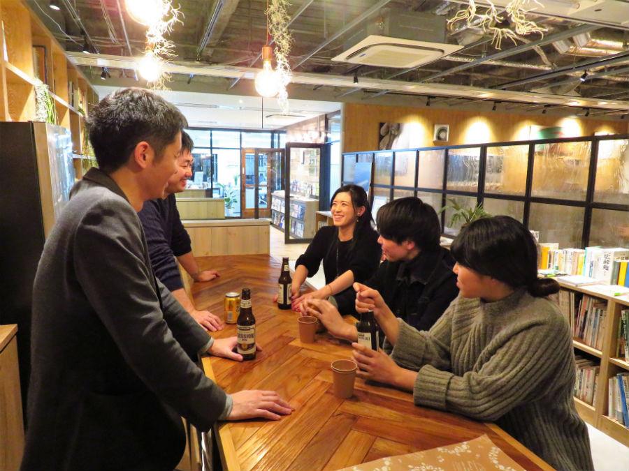 談笑する井上マネージャー(左奥)ら。ワークスペースと少し離れ、ひと息つけるバーカウンターでお酒やコーヒーを飲みながら交流を深める