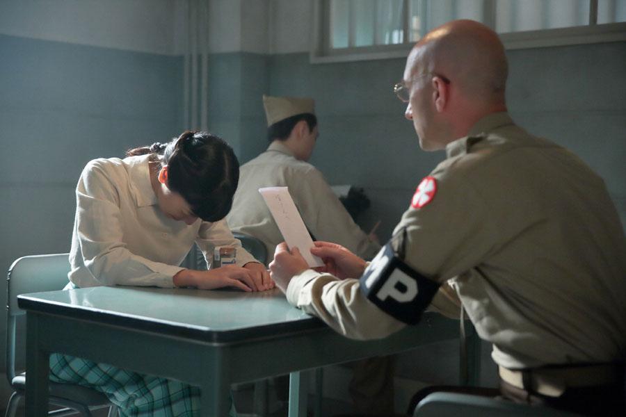 進駐軍・取調室にて、ビンガム(右・メイナード・プラント)から「萬平に会わせることはできない」と言われ、「そしたら、せめて手紙だけでも」と差し出す福子(安藤サクラ)