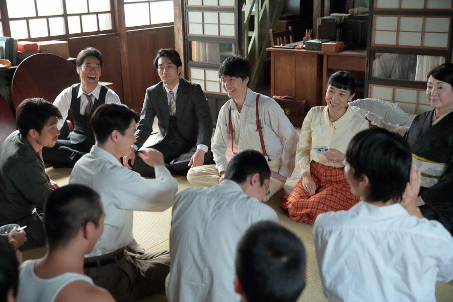 泉大津の家・1階広間で、改良したダネイホンの試食会をし、盛り上がる萬平(長谷川博己)らと社員一同
