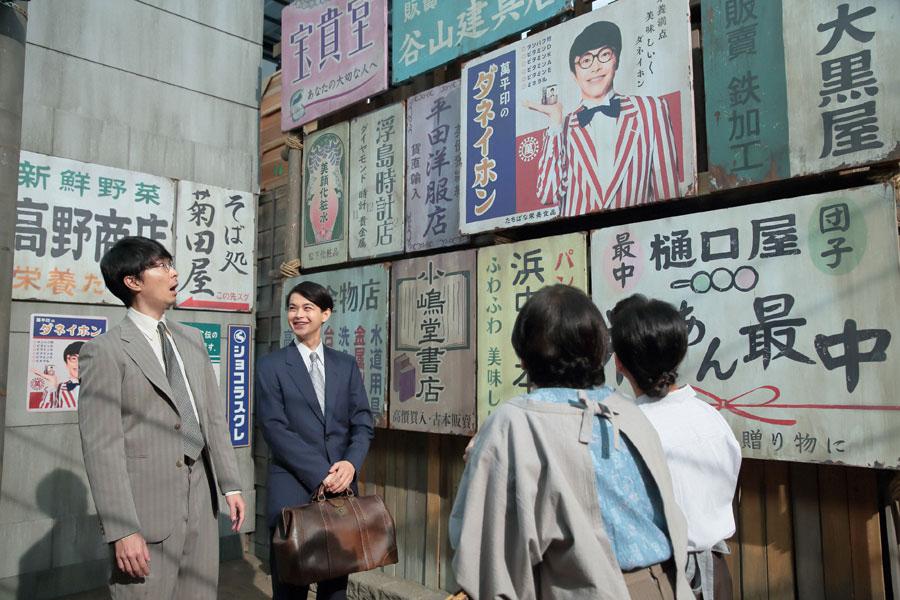 看板の効果もあり、東京の街路で見知らぬ女性たちから「萬平さん!」と声を掛けられる萬平(長谷川博己)