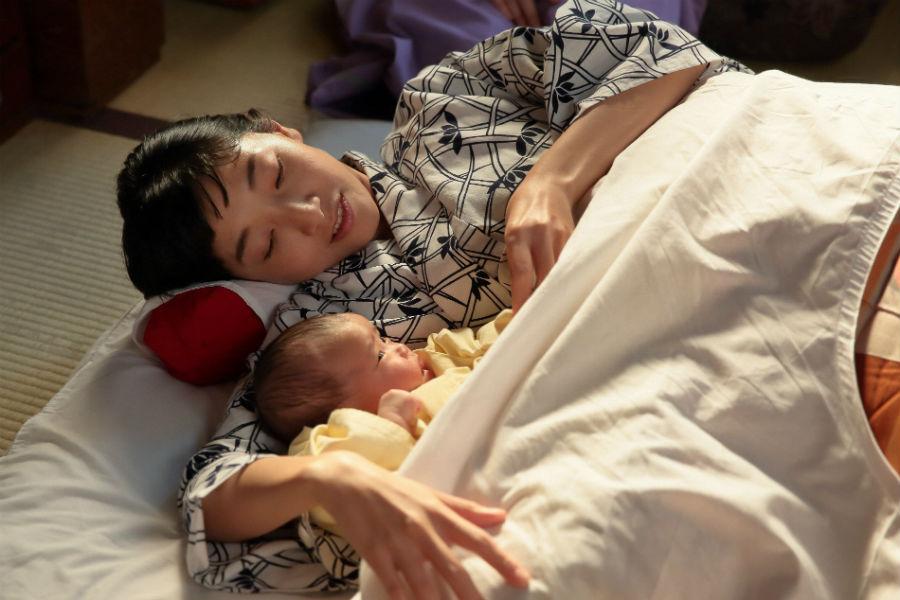 なんとか無事に出産を終え、香田家の居間で生まれたばかりの娘「幸」と添い寝する福子(安藤サクラ)