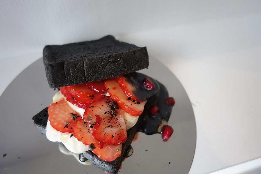 フルーツサンドには、真っ黒なパン、イチゴ、白いクリームと黒いクリームと不思議なコントラストに