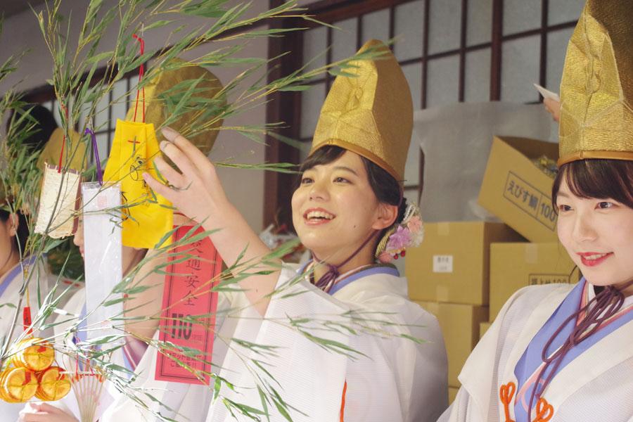 次々と差し出される福笹に縁起物をつけていく福娘(9日・今宮戎神社)