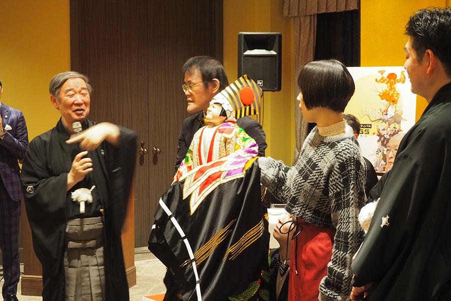 文楽の名人・吉田和生らに教わりながら人形を操るアインシュタイン稲田、宇都宮まきと、ひざまずいて人形の足を操るアインシュタイン河井