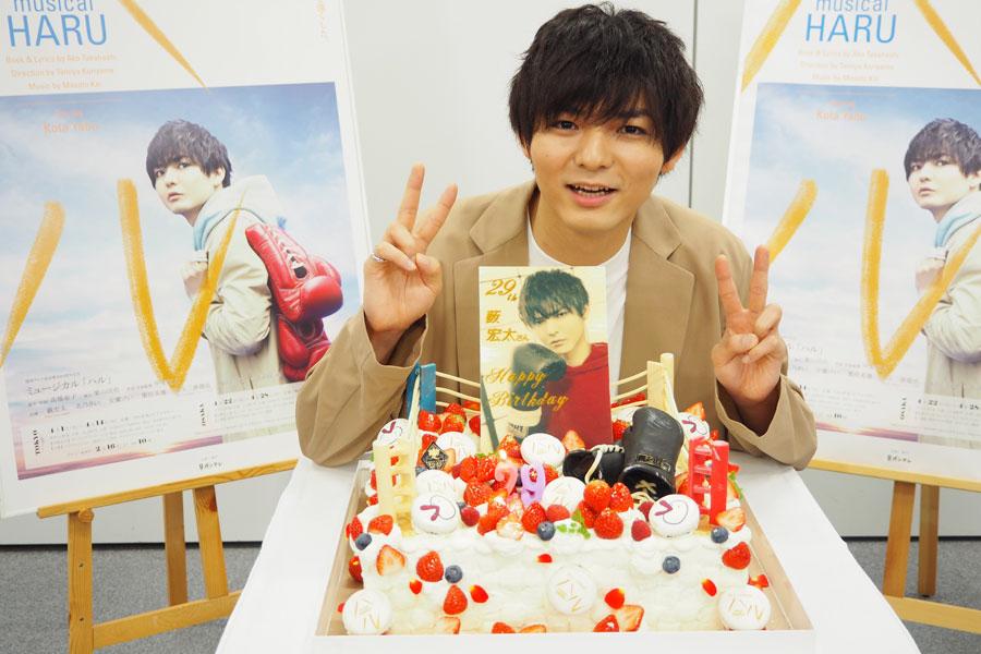 舞台に合わせてリングの形で作られたバースデーケーキを前に喜ぶ薮宏太。グローブ含めすべて食べられるとのこと